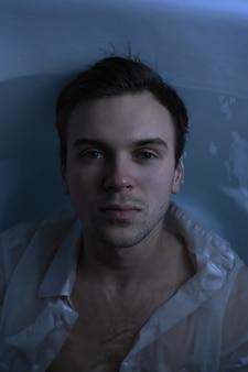 Retrato da moda em close-up de um homem bonito com a barba por fazer debaixo d'água em uma camisa branca molhada sexy, olhando para o rosto forte da câmera