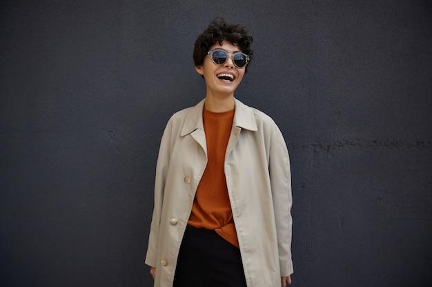 Retrato da moda estilo de vida de uma mulher jovem e elegante hippie com corte de cabelo curto usando óculos escuros, posando ao ar livre durante a pausa para o almoço, estando em alto astral e rindo alegremente