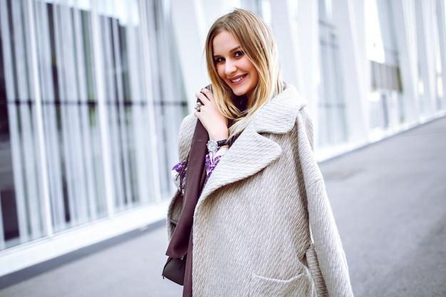 Retrato da moda estilo de vida de uma mulher muito elegante vestindo roupa da moda, lenço longo violeta, casaco de cashmere luxuoso e vestido midi, sorrindo e curtindo, fique na frente do moderno centro de negócios
