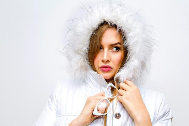 Retrato da moda estilo de vida interior de jovem loira vestindo jaqueta branca de inverno.