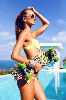 Retrato da moda glamour de uma mulher sexy deslumbrante com corpo perfeito segurando um skate brilhante, posando perto de uma vila de luxo com piscina e vista sobre a ilha exótica do oceano.