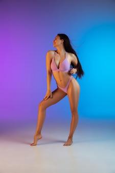 Retrato da moda jovem apto e esportiva mulher em trajes de banho de luxo elegante gradiente. corpo perfeito e pronto para o verão.