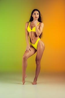 Retrato da moda jovem apto e esportiva mulher em trajes de banho elegante luxo amarelo. corpo perfeito e pronto para o verão.