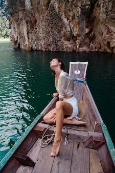 Retrato da moda jovem de férias em um barco de madeira asiático
