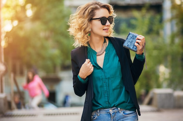 Retrato da moda jovem elegante andando na rua com uma jaqueta preta, blusa verde, acessórios elegantes, segurando uma bolsa pequena, usando óculos escuros, estilo de moda de rua de verão