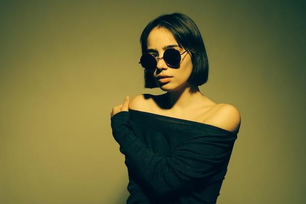 Retrato da moda jovem elegante em óculos de sol. parede colorida