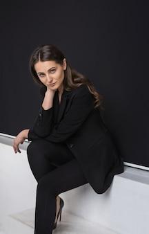 Retrato da moda jovem elegante em um terno preto