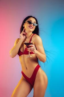 Retrato da moda jovem em forma e mulher esportiva com coquetel em um elegante maiô de luxo vermelho na parede gradiente, corpo perfeito pronto para o verão