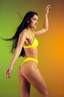 Retrato da moda jovem em forma e mulher esportiva em elegantes trajes de banho de luxo amarelos em parede gradiente