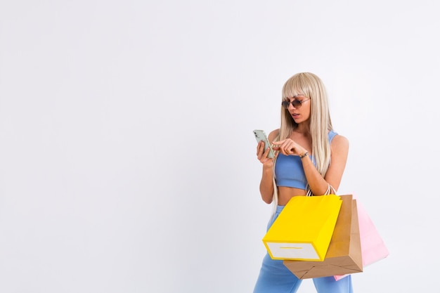 Retrato da moda jovem loira com cabelo longo lindo e liso segurando sacolas coloridas