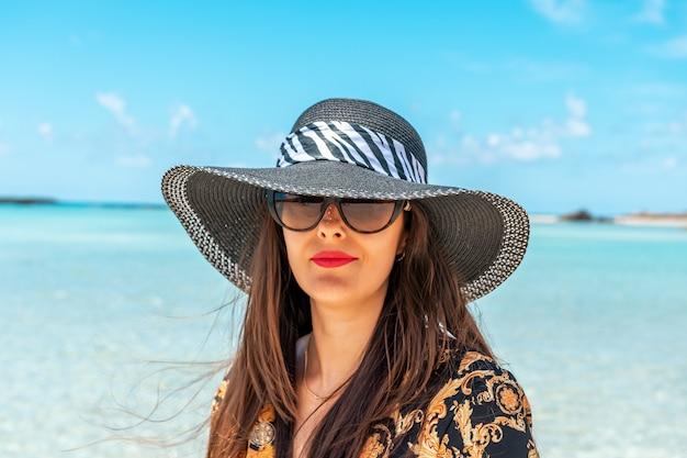Retrato da moda mulher com um chapéu em uma praia tropical