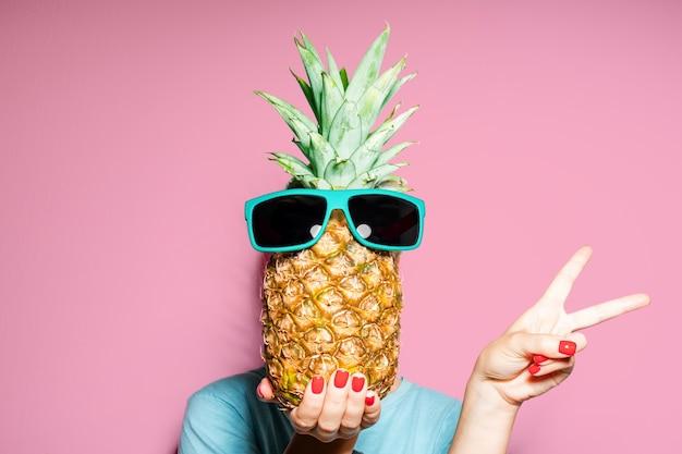 Retrato da moda mulher e abacaxi com óculos de sol escondendo a cabeça sobre a cor de fundo