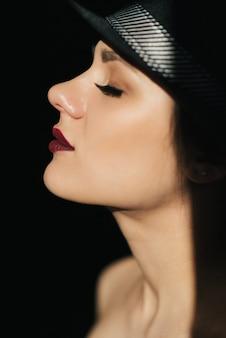 Retrato da moda no perfil de uma jovem garota sexy em um chapéu preto com batom vermelho