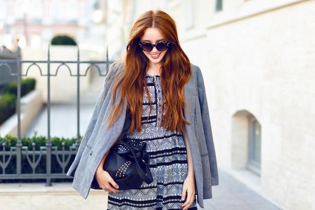 Retrato da moda outono da bela mulher ruiva posando na rua look casual elegante, casaco de caxemira, óculos de sol vintage