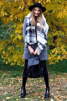 Retrato da moda outono do glamour elegante mulher posando no incrível parque da cidade, casaco elegante, mochila e chapéu vintage. caminhando sozinho, frio