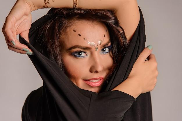 Retrato da modelo de beleza com maquiagem brilhante e tatuagem dourada no rosto e na mão