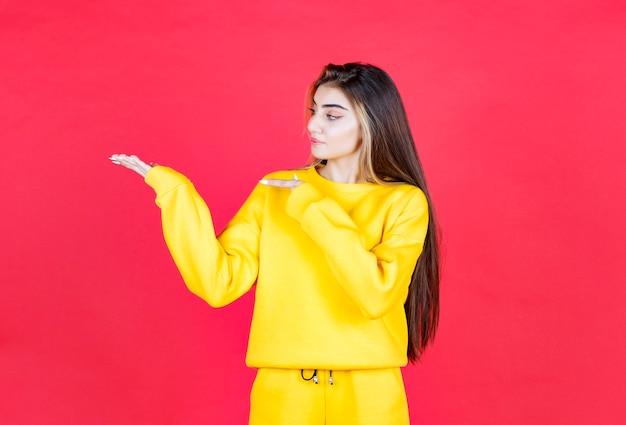 Retrato da modelo de mulher bonita em pé e apontando para a palma da mão aberta
