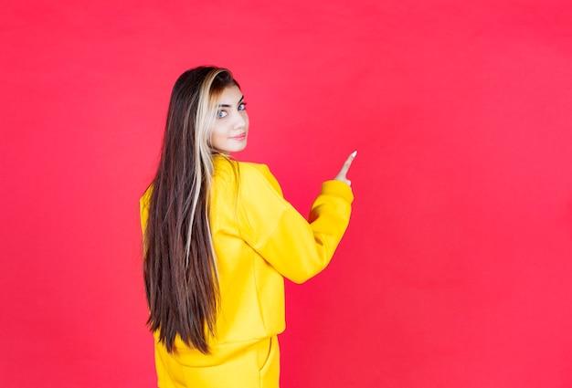 Retrato da modelo de mulher bonita em pé e apontando para cima com o dedo