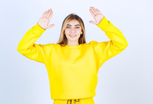 Retrato da modelo de mulher bonita em pé e levantando as mãos