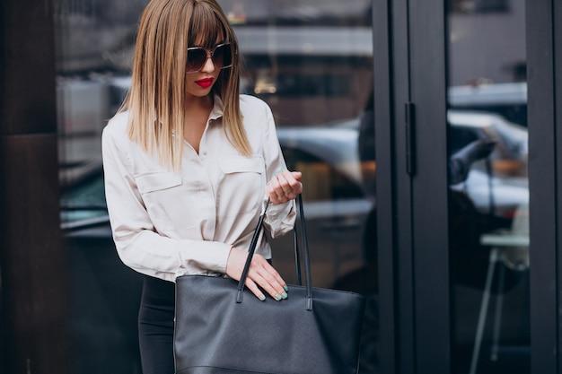 Retrato da modelo de mulher jovem e atraente olhando para a bolsa