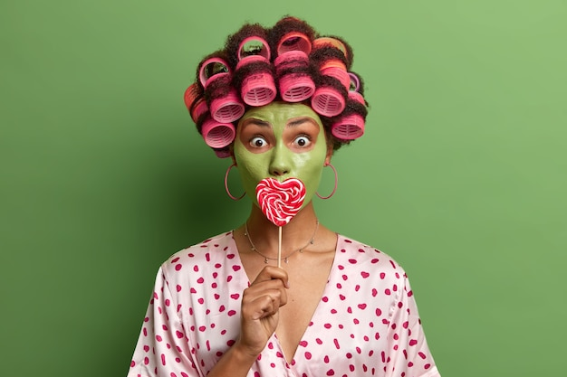 Retrato da modelo feminina atordoada cobre a boca com pirulito, usa rolos de cabelo, aplica máscara verde para cuidar da pele, faz procedimentos de spa em casa, usa robe de seda, tem expressão facial de surpresa.
