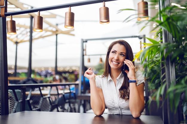 Retrato da morena caucasiano lindo sentado no café no shopping e fofocando por telefone.