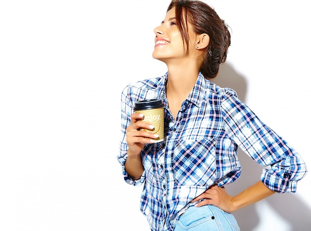Retrato da mulher adolescente legal à moda bonita na camisa quadriculado, mantendo o copo de café plástico copie o espaço disponível.