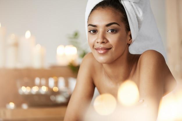 Retrato da mulher africana bonita com a toalha na cabeça que sorri descansando no salão spa.