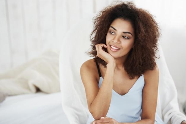 Retrato da mulher africana bonita sonhadora na roupa de noite que sorri sentado na cadeira em casa. copie o espaço.
