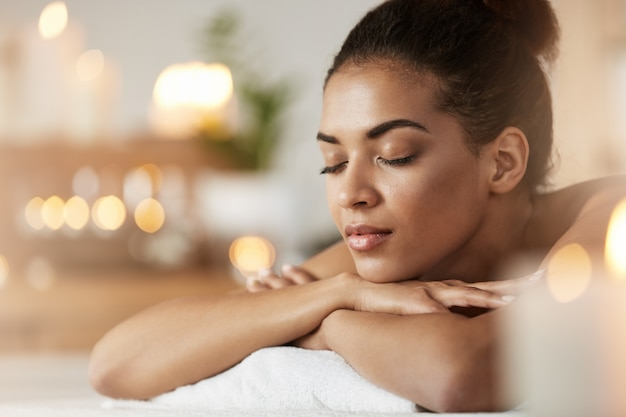 Retrato da mulher africana macia com os olhos fechados que descansam o relaxamento no spa resort.