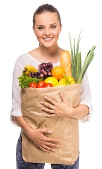 Retrato da mulher alegre que guarda o saco de compras.