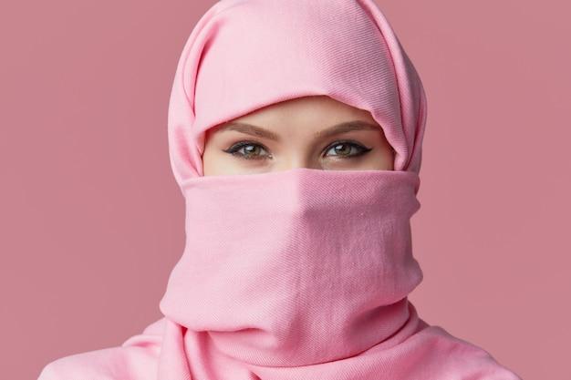 Retrato da mulher árabe muçulmana nova que veste o hijab colorido. aponta o dedo para o lado.