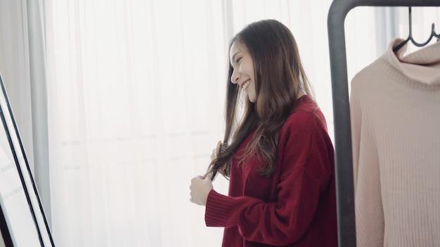 Retrato da mulher asiática atrativa bonita que penteia seu cabelo e que escolhe a roupa em seu vestuario em casa.