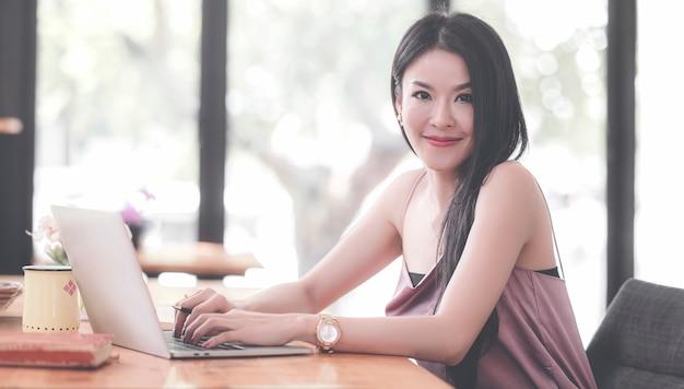 Retrato da mulher asiática bonita nova que sorri e que olha a câmera ao sentar-se e ao trabalhar com o escritório do laptop em casa.