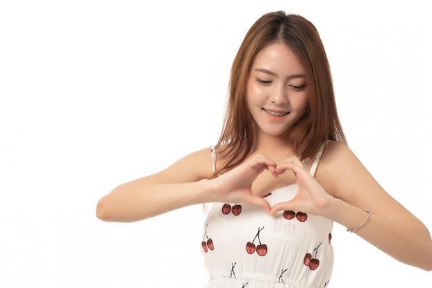 Retrato da mulher asiática bonita que está de pé fazendo uma forma do cervo com dedos. linda garota feliz em branco; amar.