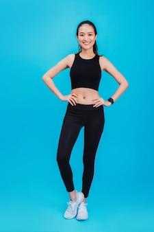 Retrato da mulher asiática bonita segura da aptidão que está após o exercício isolado na cor azul.