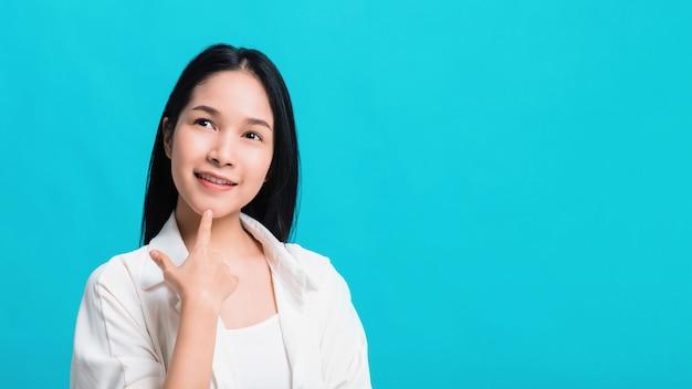 Retrato da mulher asiática bonita segura que pensa e que sorri isolado no fundo azul da cor.