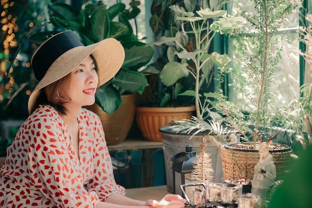 Retrato da mulher asiática com chapéu que sorri no tom da cor do vintage do café da cafetaria do verão.
