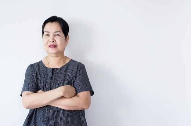 Retrato da mulher asiática idosa bonita que está os braços transversais e que olha a câmera interna, feliz e cara do sorriso, espaço da cópia para o texto no fundo branco