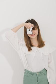 Retrato da mulher asiática nas cintas usando uma câmera do vintage sobre o cinza no estúdio. fotografia em ação.