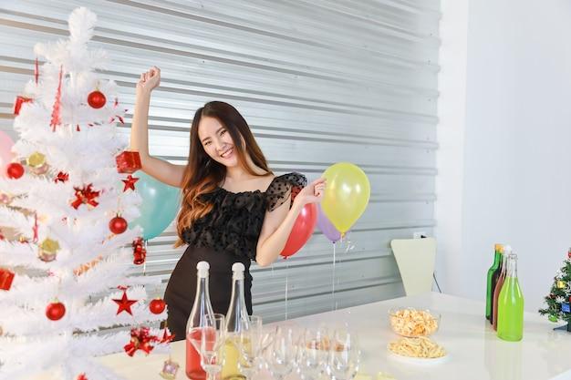 Retrato da mulher asiática nova bonita feliz e sorridente na festa de natal com comida e bebida e festa de balão cheia de cores.