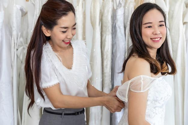 Retrato da mulher asiática que escolhe o vestido em uma loja com assistente do alfaiate.