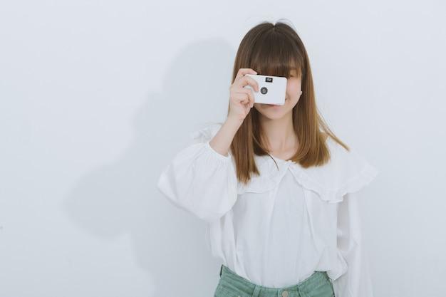 Retrato da mulher asiática que usa uma câmera do vintage, vista lateral, copyspace. fotografia em ação.