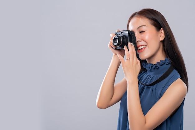 Retrato da mulher asiática que usa uma câmera do vintage, vista lateral, fotografia na ação.