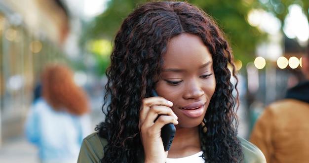 Retrato da mulher atraente multirracial falando no smartphone ao ar livre enquanto usa o celular p ...