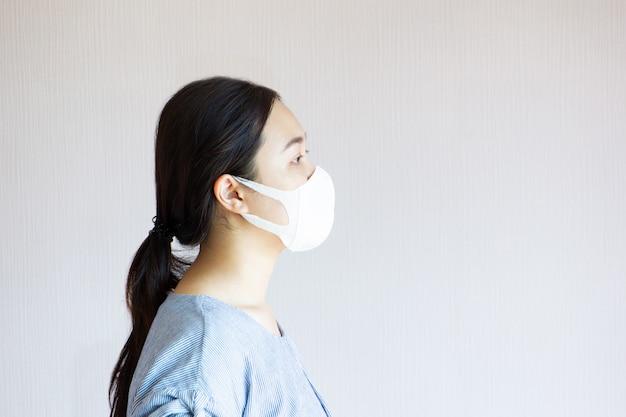 Retrato da mulher bonita asiática que veste um fim da máscara protetora da higiene acima.