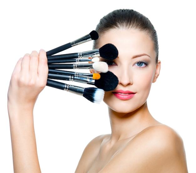 Retrato da mulher bonita com pincéis de maquiagem perto do rosto atraente.
