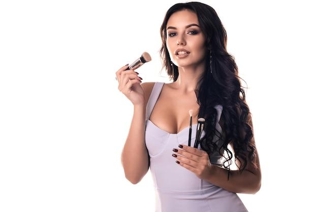Retrato da mulher bonita com pincéis de maquiagem