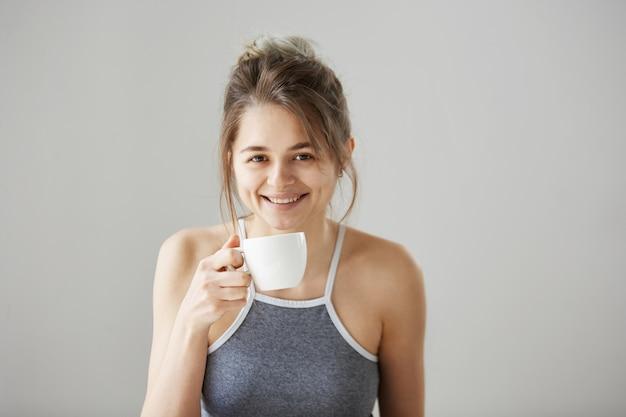 Retrato da mulher bonita feliz nova que sorri guardando a xícara de café bebendo na manhã sobre a parede branca.