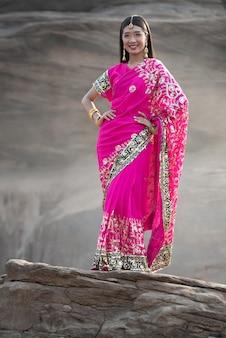 Retrato da mulher bonita nova asiática que veste o vestido indiano tradicional que está no fundo da rocha.